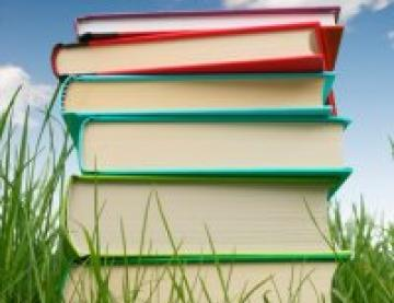 Colourful stack of hardback books in the grass