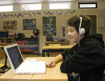 Teenager wearing headphones and sitting at a classroom desk with a laptop on
