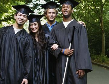 Four smiling students in graduation gowns and caps. The student on the far right is holding a long cane.