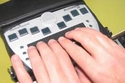 Fingers reading a Braillenote Touch