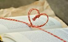 An open book with red cord twisted into a heart outline over the open pages