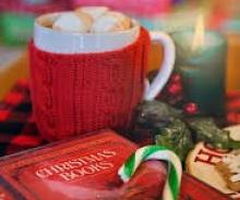 Hot Chocolate and marshmallows in a red mug, lit candle, christmas books and candy cane