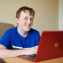 16 year old smiling Charlie wearing a blue t-shirt sat at a table with a red laptop