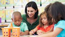 classroom, teacher sat with 3 children learning at tables