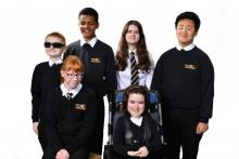 Six smiling students in NCW uniform, boys and girls.