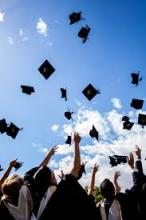 students in gowns groupedtogether and throwing their mortar board hats into the air