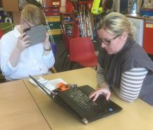 Female teacher with a male learner in class using iPads at Priestley Smith School