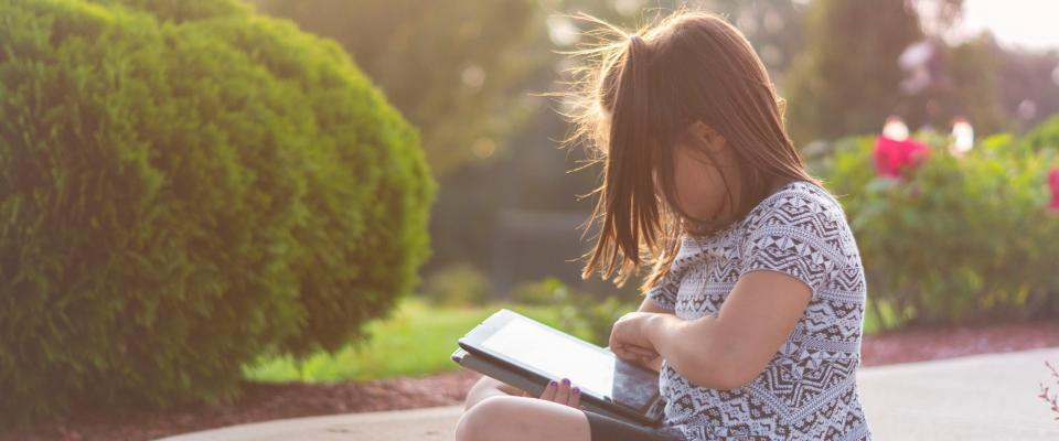 young girl sat outside in a sunny garden reading on a tablet