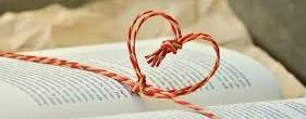 An open book with a piece of red cord twisted into a heard outline across the open pages