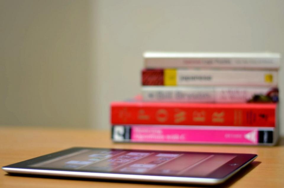 a pile of books and an iPad/tablet on a deask