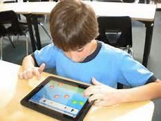 boy of 8-9 sitting at a desk, with an electronic tablet in front of him. it is turned on and his head is bent over it.