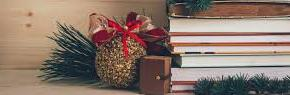 stack of books with pine cones, red ribbon and decorations