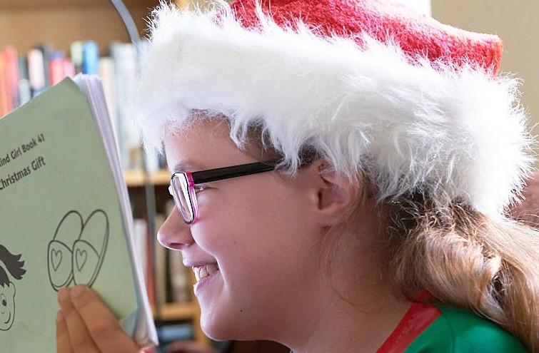 Keira, a smiling girl reading an 'Abi' book
