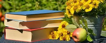 a pile of books outside on a summery day on grass with sunflowers and an apple