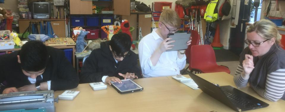 Physics lesson with teacher and 3 male partially sighted learners using iPads.
