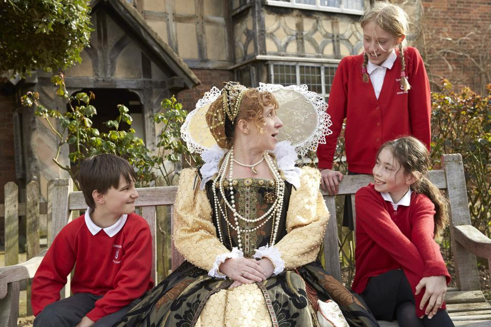 Queen Elizabeth the first outside a tudr style house with 3 modern school children