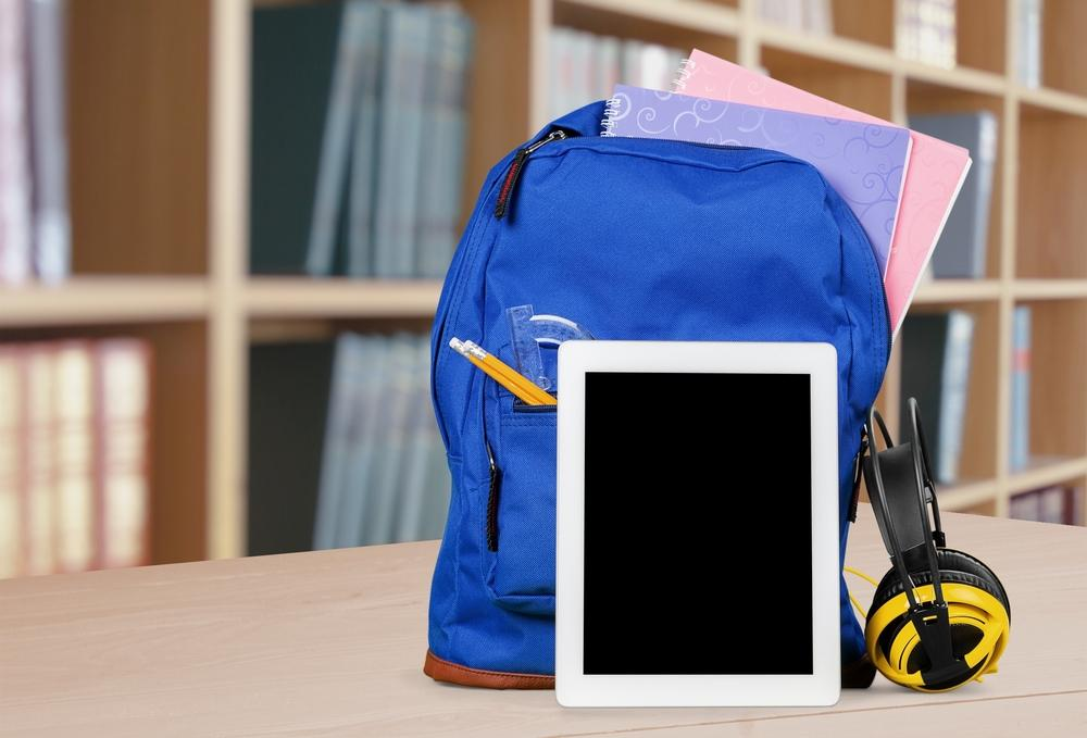 Rucksack packed for school on a table with an iPad. Shelf of books in background