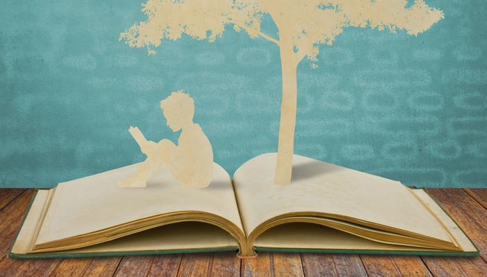 open book with silhouette of a boy sitting down reading and  fountain of letters