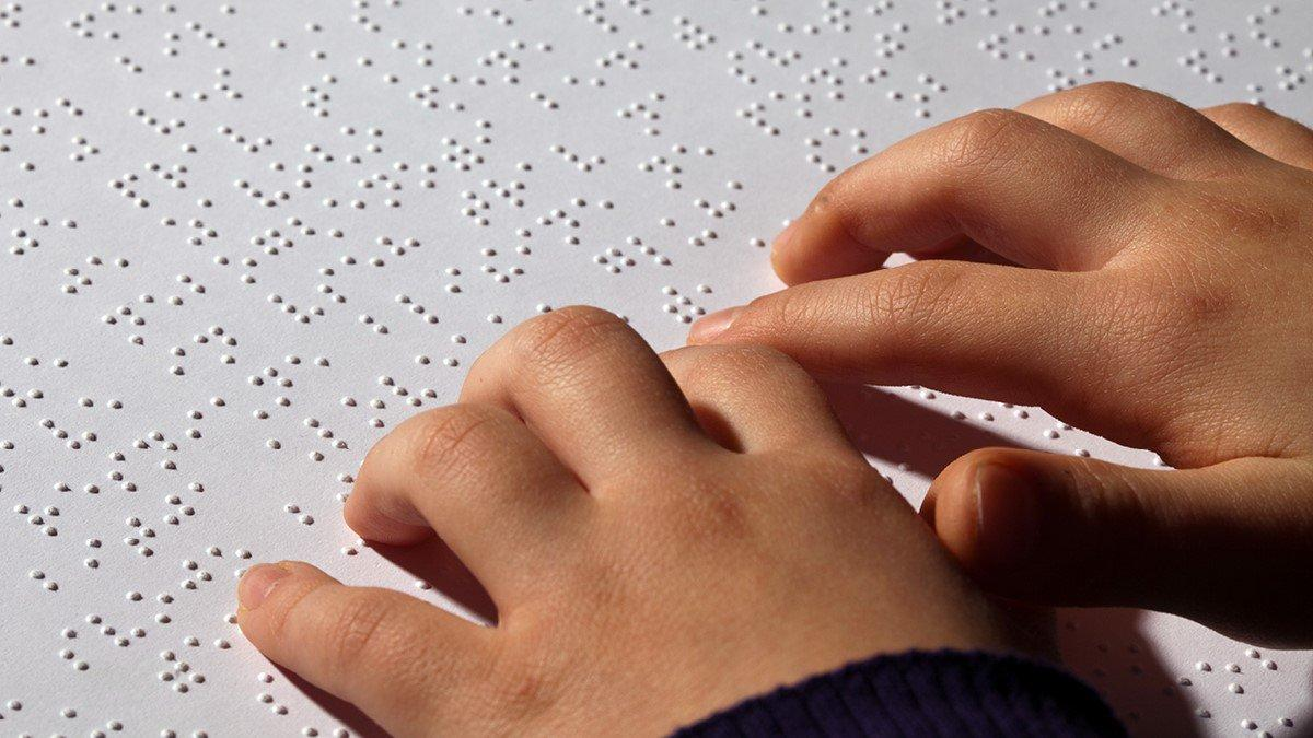 braille text with hand of a child scanning it