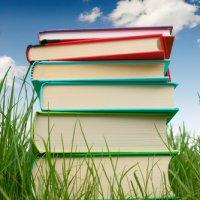 Stack of colourful hardback books on grass, with blue sky inthe background