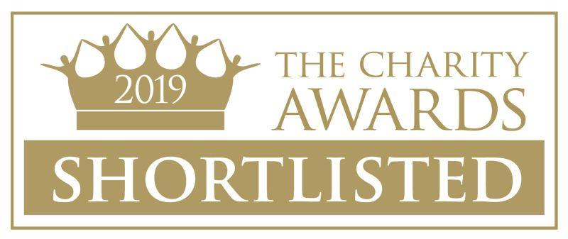 Charity Awards logo, a gold crown with people holding hands as the uprights. gold text 'Charity awards 2019 shortlisted'